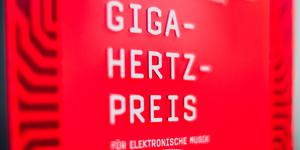 "Red plaque with ""Giga-Hertz-Award"" in white letters"