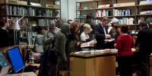 People stand in front of a desk full of books