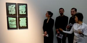 Four people looking at four images on which green brushstrokes are visible on a black background