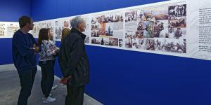 Five people look at pictures in an exhibition, which are hanging on a blue background