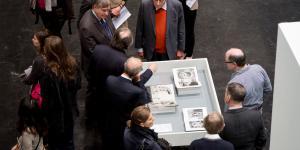 Die Besucher stehen um Herrn Weibel und eine weiße Vitrine, in der mehrere Bücher aufgeschlagen liegen.
