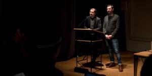 Zwei Personen stehen vor einem Pult und sprechen zum Publikum