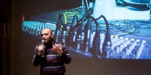 Ein Mann steht vor einer Leinwand und spricht zum Publikum.