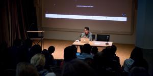 Ein Mann sitzt am Tisch und spricht zum Publikum.