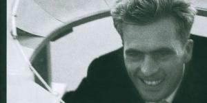 Schwarzweißes Foto eines lächelnden Mannes, weiße Schrift.