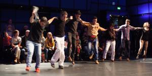 Junge Männer stehen in einer Reihe und tanzen