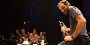 Ein Mann sitzt auf dem Boden und präsentiert verschiedene Instrumente