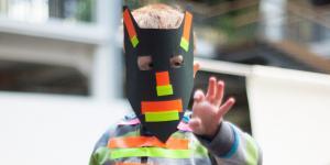 Ein Junge mit einer selbstgebastelten Maske und verschiedene Klebestreifen auf der Kleidung