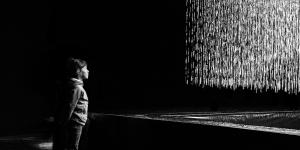 Black and white photo of the installation 3D WATERMATRIX in which water falls to the ground and generates 3D shapes. A person is watching the insatallation