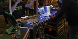 Zwei Männer stehen sich gegenüber und testen ihr tablet bzw. laptop