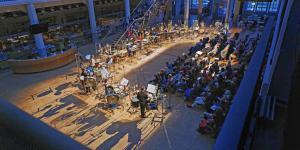 Menschen sitzen vor verschiedenen Schlaginstrumenten, die von Personen gespielt werden