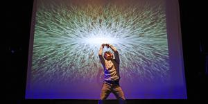 A man performs in front of a canvas on which a luminous ball can be seen