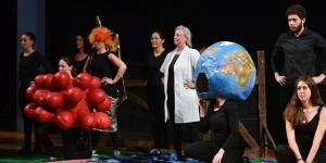 Several people standing in a row. In between a globe and molecules made of paper mache