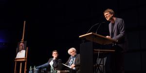 Links: Eine Staffelei mit einem Bild eines Mannes mit einem Turban. Mitte: Zwei Männer sitzen auf Stühlen. Rechts: Ein Mann steht an einem Podest und spricht zum Publikum.