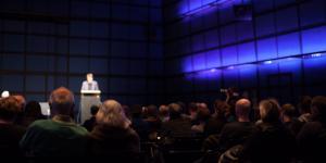 Ein Mann steht am Podest und spricht zum Publikum