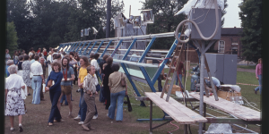 A crowd of people stands next to a large outdoor installation, you can see trees in the background