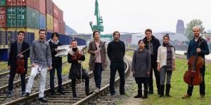 Das IEMA-Ensemble steht auf Schienen vor einer Hafenkulisse mit Containern und einem Kran