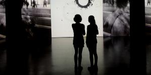 Two visitors in front of a Tambellini video canvas