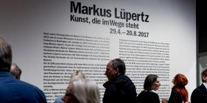 The picture shows visitors in front of an information board for Markus Lüpertz