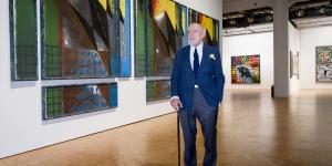 Markus Lüpertz steht im Anzug vor einem bunten Bild in der Ausstellung