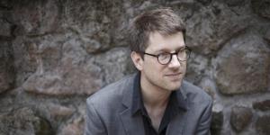 Ein Mann mit Brille sitzt vor einer Steinwand