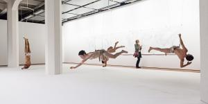 Five dancers hanging on ropes upside down in the exhibition space.