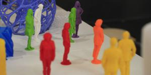 A lot of little colourful igurines printed with the 3D-printer are standing every which way on a table.