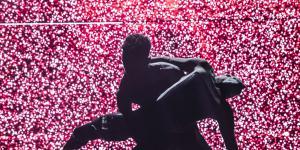 Die Silhouette zweier ineinander verwobener TänzerInnen vor einem pink angeleuchteten HIntergrund