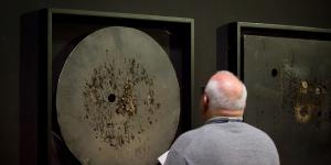 The photo shows the back of a bald man in front of a work by Aldo Tambellini.