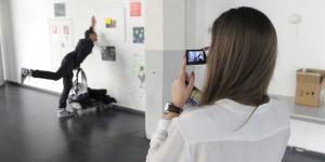 Eine junge Frau fotografiert einen für das Bild posenden Mann, der so tut, als ob er mit einem Rollwagen gegen die Wand fährt.