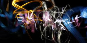 Using a flash light and a camera with longterm exposure, a light graffiti has been created. In abstract forms there are whirling yellow, white and blue stripes across the black background.