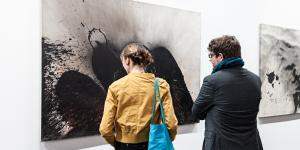 Two people standing in front of Otto Piene's images.