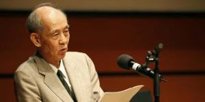 Hiroshi Kawano during his presentation. He is wearing a light suit, in his hands he holds his manuscript.
