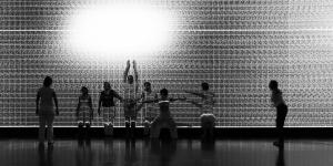 A group of dancers is moving in front of a wall with black and white projections.