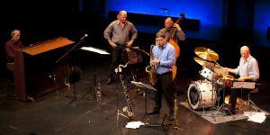 Fünf Musiker in einer Bühnensituation sind zu sehen.