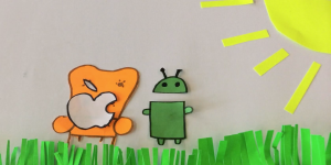 Still of an animation workshop in which the bitten apple sits on a cosy chair next to the android-mascot.