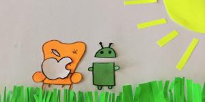 Standbild eines Trickfilms auf dem der abgebissene Apfel von Apple neben dem Maskottchen von Android auf einem Sessel sitzt.