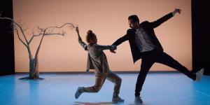 Ein Tänzer und eine Tänzerin halten sich an der Hand. Im Hintergrund ein Baum.