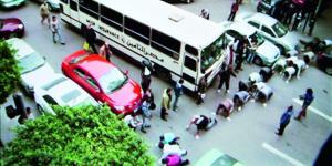 Strassenkreuzung: Menschen überqueren sie auf Knien