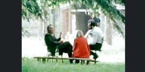 Zwei Männer und eine Frau sitzen auf einer Wiese unter einem Baum. Ein Mann hält eine Kamera in der Hand.