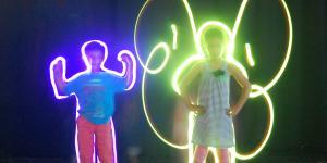 Ein Junge und ein Mädchen posieren vor der Kamera. Mit Taschenlampen und Langzeitbelichtung entstehen um ihre Konturen fantastische Silhouetten, wie z.B. ein Schmetterling