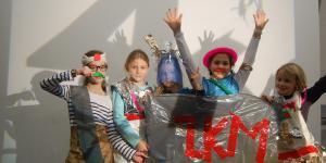 Eine Gruppe Mädchen, die sich aus alltäglichen Gegenständen Outfits gebastelt haben, halten ein Banner mit dem Schriftzug ZKM in rotem Klebeband vor sich.