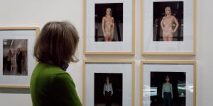 Eine Frau blickt auf mehrere Fotografien