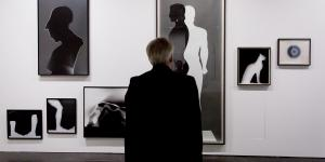 A man is standing in front of different images in black and white