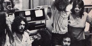 Das Schwarzweiß-Bild zeigt eine Gruppe langhaariger junger Menschen vor kleinen Bildschirmen