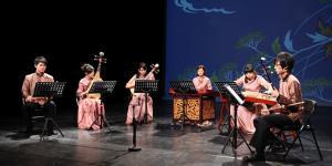 Sechs Musiker in traditioneller chinesischer Kleidung mit ihren Instrumenten auf der Bühne
