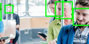 The photo shows several people in a tram, all looking at their smartphone. Above their faces lies the face recognition symbol in neon green color.