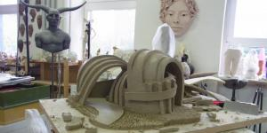A model of a surrealistic house out of clay is sitting on a panel of wood.