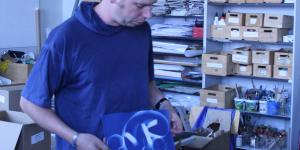 Ein Mann hält ein Fotogramm vor sich auf dem sich die Kontur eines schleifenförmigen Gegenstandes abzeichnet.