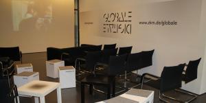 Die Medialounge im ZKM. Schwarze Sessel und weiße Sitzwürfel vor einer Leinwand.